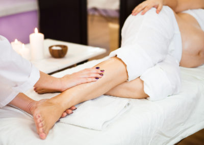Young pregnant woman relaxing with hand leg massage at beauty sp