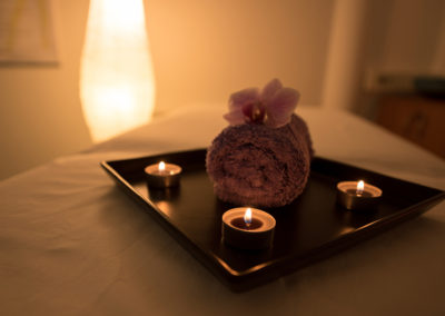 Keep-in-Touch Massage salon decor in massage room with candles, towel and an orchid.